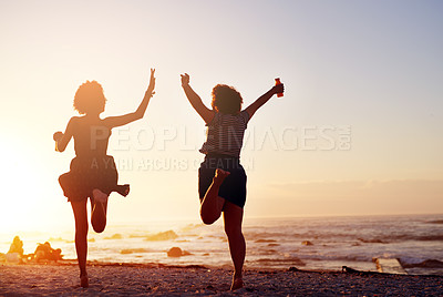 Buy stock photo Rearview shot of two unrecognizable young women jumping up in joy while walking along the beach at sunset