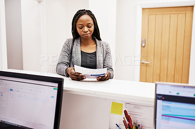 Buy stock photo Shot of a beautiful young woman reading a brochure at the reception area of a beauty clinic