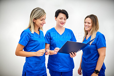 Buy stock photo Shot of three young female nurses discussing some paperwork against a grey background