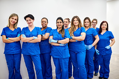 Buy stock photo Portrait of a group of female nurses posing with their arms folded at a clinic