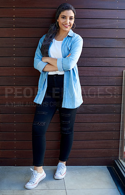 Buy stock photo Full length shot of an attractive young woman wearing a headscarf and posing alone against a wooden background outside
