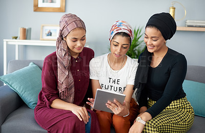 Buy stock photo Cropped shot of three attractive young women wearing headscarves and using a tablet while sitting on a sofa