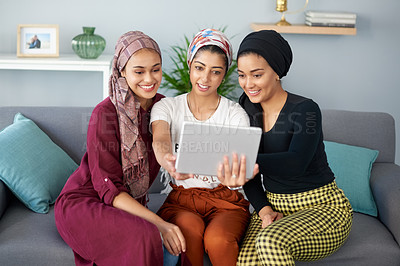 Buy stock photo Cropped shot of three attractive young group of women wearing headscarves and posing for a selfie with a tablet