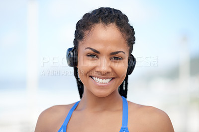 Buy stock photo Portrait of an attractive young woman wearing headsets while exercising outdoors
