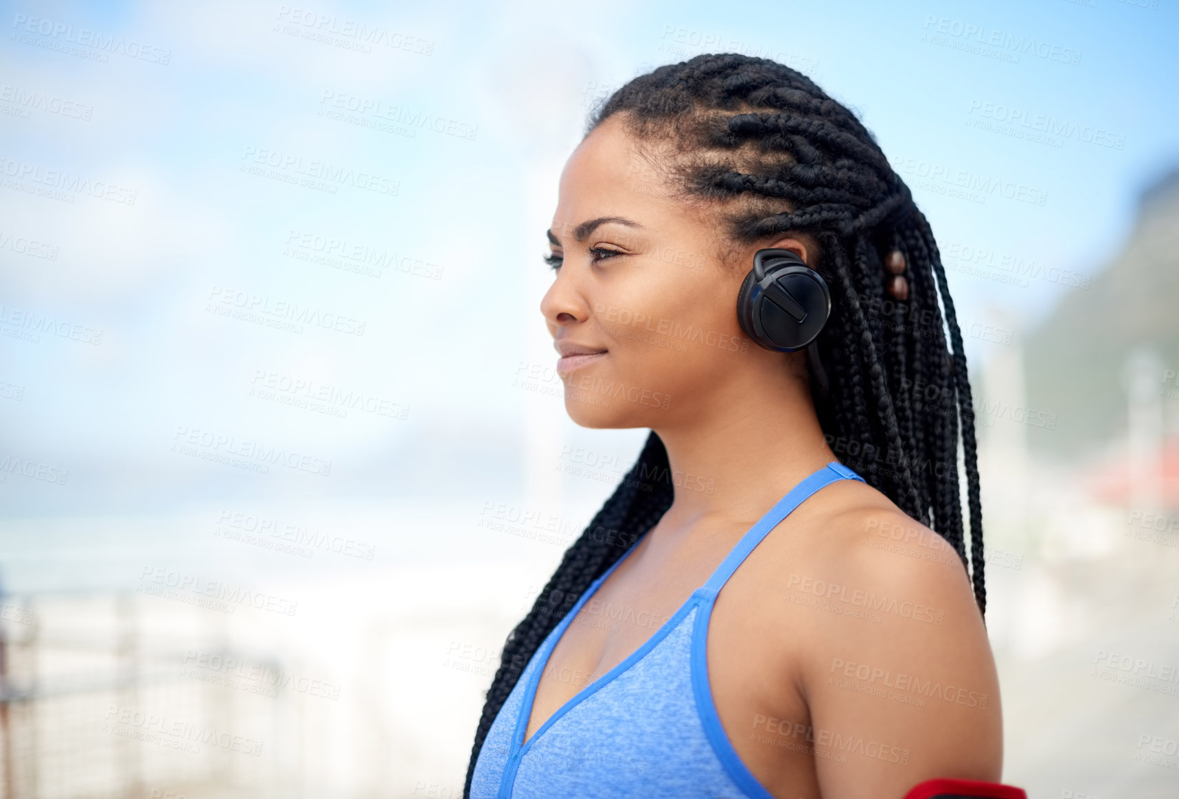 Buy stock photo Shot of an attractive young woman wearing headsets while exercising outdoors