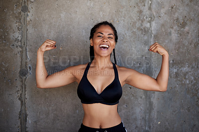 Buy stock photo Shot of an attractive young sportswoman showing off her bicep muscles against a wall outdoors