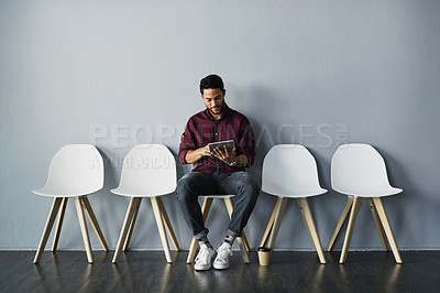 Buy stock photo Full length shot of a handsome young businessman using his tablet while sitting against a gray studio background