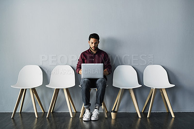 Buy stock photo Full length shot of a handsome young businessman using his laptop while sitting against a gray studio background