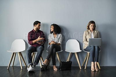 Buy stock photo Full length shot of three young businesspeople using their technology while sitting against a gray background in the studio