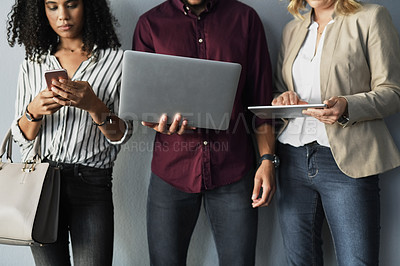 Buy stock photo Cropped shot of three young businesspeople using their technology while standing against a gray background in the studio