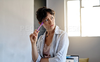 Buy stock photo Shot of a young woman looking thoughtful while holding a pen