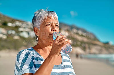 Buy stock photo Cropped shot of an attractive senior woman drinking water from a bottle on the beach during the day