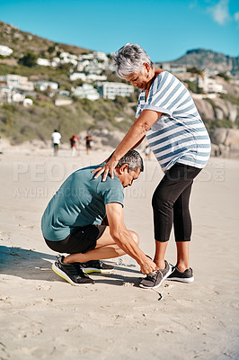 Buy stock photo Full length shot of an affectionate senior couple helping each other tie their shoes on the beach during the day