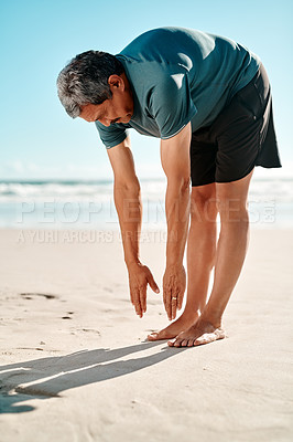 Buy stock photo Full length shot of a handsome senior man standing and stretching on the beach during the day