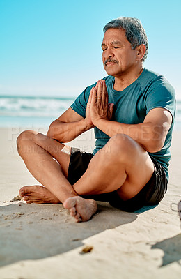 Buy stock photo Full length shot of a handsome senior man sitting and meditating on the beach during the day