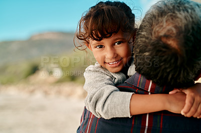 Buy stock photo Cropped shot of an adorable young girl smiling at the camera while her grandfather carries her on the beach