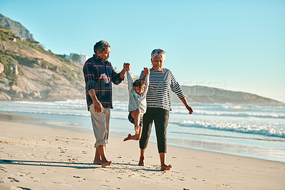 Buy stock photo Full length shot of a happy senior couple playing with their granddaughter on the beach during the day