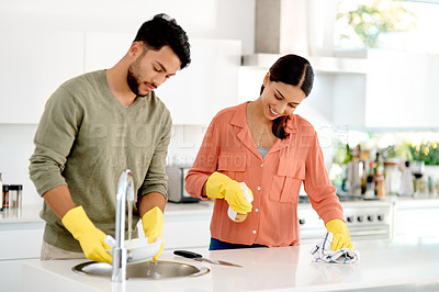 Buy stock photo Cropped shot of a happy young couple doing the dishes together