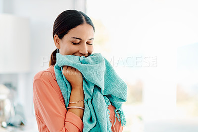 Buy stock photo Cropped shot off a young woman smelling a freshly washed towel at home