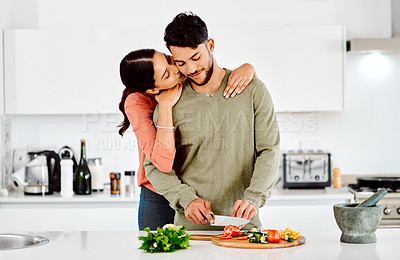 Buy stock photo Shot of a woman embracing her boyfriend while he chops vegetables