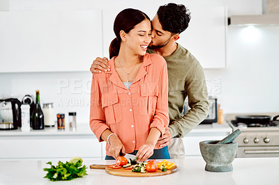 Buy stock photo Shot of a man embracing his girlfriend while she chops vegetables