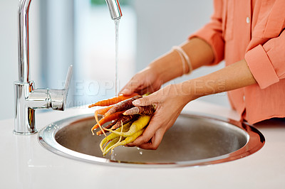 Buy stock photo Cropped shot of an unrecognizable woman rinsing vegetables at home