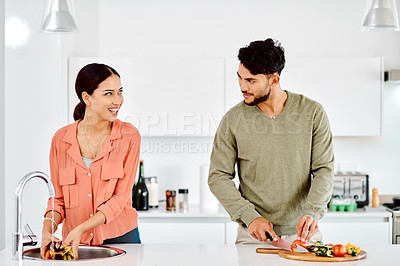 Buy stock photo Shot of a couple preparing a meal together in the kitchen