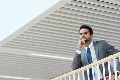 Buy stock photo Shot of a young businessman looking thoughtful while standing in an office