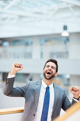 Buy stock photo Shot of a young businessman cheering in an office