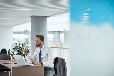 Buy stock photo Shot of a young businessman cheering while working on a laptop in an office