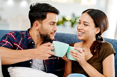 Buy stock photo Shot of an affectionate young couple having coffee together in their living room at home