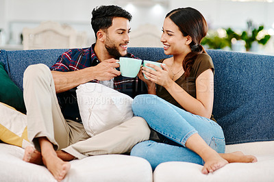 Buy stock photo Full length shot of an affectionate young couple having coffee together in their living room at home