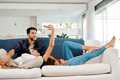 Buy stock photo Full length shot of an affectionate young couple taking selfies together in their living room at home