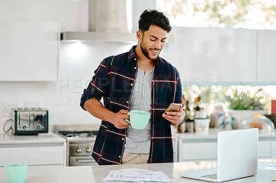Buy stock photo Shot of a handsome young man drinking coffee and using a cellphone in his kitchen at home
