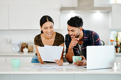 Buy stock photo Shot of an affectionate young couple going over their finances in their kitchen at home