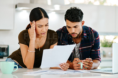 Buy stock photo Shot of a young couple looking stressed out while going over their finances in their kitchen at home