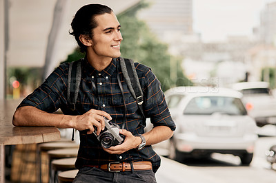 Buy stock photo Cropped shot of a handsome young man smiling and holding his camera while being outside during the day