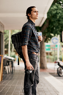 Buy stock photo Cropped shot of a handsome young man standing and holding his camera while being outside during the day