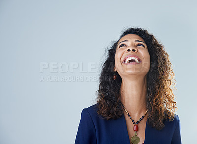 Buy stock photo Cropped shot of an attractive mature woman standing and laughing against a gray background in the studio