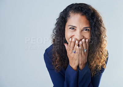 Buy stock photo Cropped shot of a playful mature woman placing her hands over her mouth while standing against a gray background