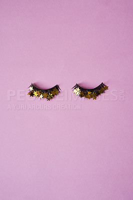 Buy stock photo Studio shot of a pair of false eyelashes with golden stars on them against a pink background