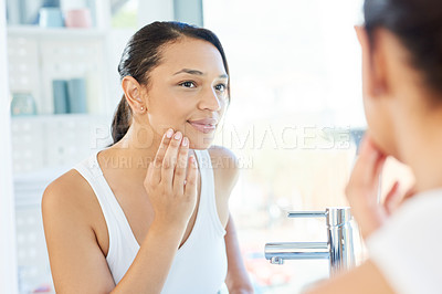 Buy stock photo Cropped shot of an attractive young woman analyzing her skin in her bathroom mirror at home