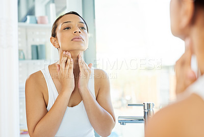 Buy stock photo Cropped shot of an attractive young woman feeling her pulse on her neck while standing in front of the bathroom mirror at home