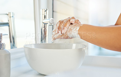 Buy stock photo Cropped shot of an unrecognizable young woman washing her hands in the bathroom basin at home