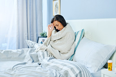 Buy stock photo Shot of an uncomfortable looking young woman lying in bed while being sick at home