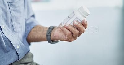 Buy stock photo Cropped shot of an unrecognizable man taking his medication at home