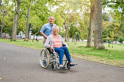 Buy stock photo Full length portrait of a smiling senior man pushing his happy senior wife in a wheelchair in the park