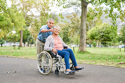 Buy stock photo Full length shot of a senior man pushing his happy senior wife in a wheelchair in the park