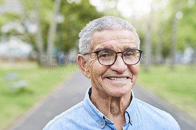 Buy stock photo Cropped portrait of a retired senior man standing and smiling in the park alone during the day