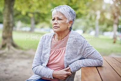 Buy stock photo Cropped shot of a retired senior woman sitting at a picnic table alone in the park during the day